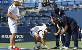David Ferrer examines the spot where water is seeping on to the court