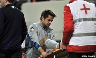 Lukasz Fabianski is stretchered off with a knee injury as Arsenal lose to Olympiakos