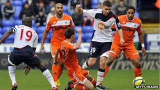 Swansea City's Josh McEachran battles for the ball with Bolton's Joe Riley