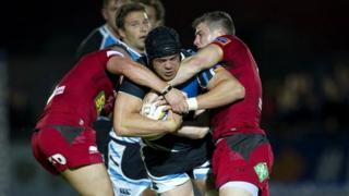 Tom Ryder (centre) is halted by Scarlets' Scott Williams and Tavis Knoyle (right)
