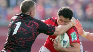 Edinburgh prop John Yapp tackles Munster winger Dougie Howlett at Thomond Park