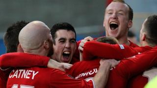Cliftonville players celebrate a goal against Linfield