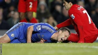 John Terry (left) shows his agony after an accidental collision with Luis Suarez