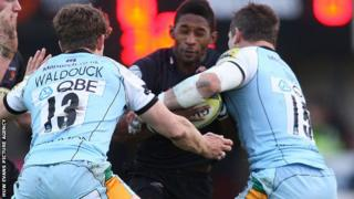 Tonderai Chavhanga is stopped by Northampton's Dominic Waldouck and Tom May
