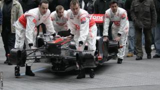 Mclaren mechanics carry the chassis of the McLaren Mercedes MP4-26