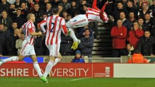 Stoke City's Trinidadian striker Kenwyne Jones (right) celebrates scoring their second goal as teammates US defender Geoff Cameron (second left) and Irish striker Jonathan Walters (left) join in