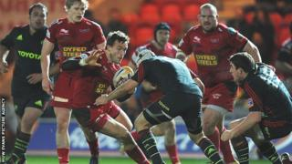 Andy Fenby of Scarlets takes on Munster's Duncan Williams