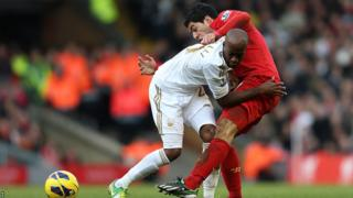 Swansea City's Dwight Tiendalli battles with Liverpool striker Luis Suarez for the ball