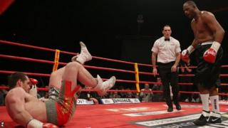 David Price (left) is knocked down by Tony Thompson