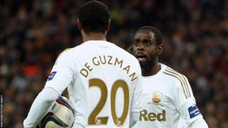After scoring twice, Nathan Dyer pleads with team-mate Jonathan de Guzman to take over as the penalty taker. De Guzman refuses, scores from the spot and adds another goal in added time to round off a thumping 5-0 win over Bradford City in the Capital One Cup final
