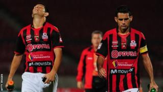 Deportivo Lara players Miguel Mea Vitali (R) and Marcelo Maidana after their Copa Libertadores defeat by Chile's Universidad de Chile