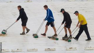 Groundstaff mop water off the Wellington covers