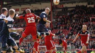 Huddersfield striker James Vaughan heads in a goal at Bristol City