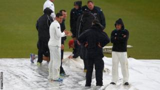 New Zealand's players help the ground staff put the covers on at Grace Road