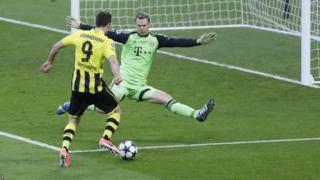 Bayern goalkeeper Manuel Neuer blocks a shot by Dortmund's Robert Lewandowski