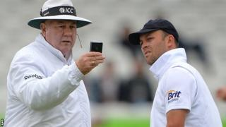 Umpire Steve Davis checks the light meter, watched by England's Jonathan Trott