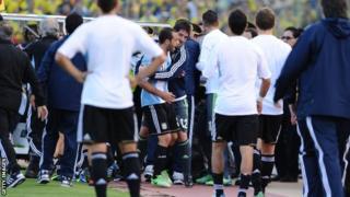 Javier Mascherano is held back by Argentina staff