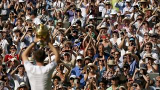 Andy Murray shows the crowd the trophy