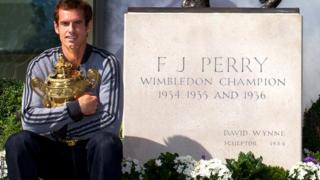 Andy Murray poses with trophy at Fred Perry statue