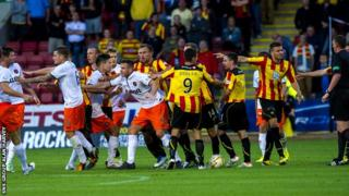 Referee Craig Thomson (far right) looks on as Thistle and United players scuffle