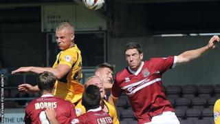 Newport County and Neorthampton battle for the ball in the air