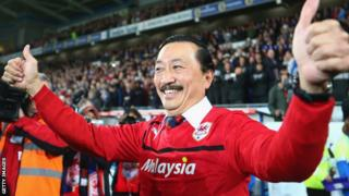 Vincent Tan celebrates in a red Cardiff City shirt