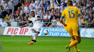 Swansea player Wayne Routledge scores the opening goal