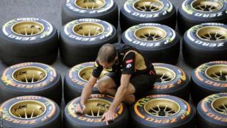 A man marks tyres in pit lane