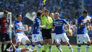 A player is booked during a Sampdoria v Genoa derby match