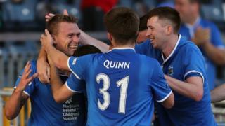 Linfield players Niall Quinn and Billy Joe Burns congratulate last-gasp goalscorer Peter Thompson at Windsor Park