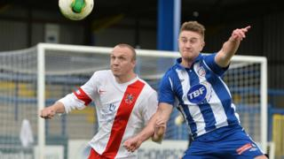 Ards defender Andy Hunter competes against striker Shane Jennings who scored in Coleraine's 2-1 win at the Showgrounds