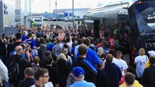 Football fans watch as the Newcastle United team arrive prior to the Barclays Premier League match between Cardiff City and Newcastle United at Cardiff City Stadium