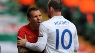 Wayne Rooney restrains Bellamy as Wales lose 2-0 to England in a Euro 2012 qualifier in Cardiff