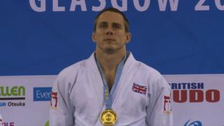Euan Burton with gold medal on podium