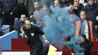 Assistant referee David Bryan is struck by a flare during the Aston Villa v Tottenham Hotspur match