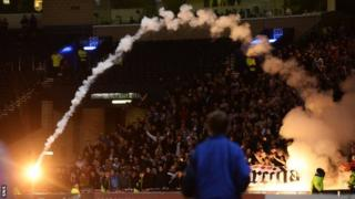 A flare flies from the area populated by Croatia fans