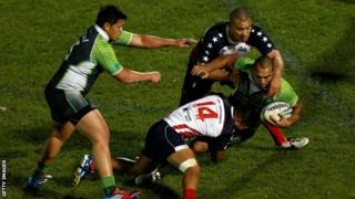 Zeb Taia of the Cook Islands tries to get through the USA defence