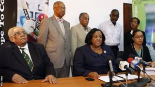 Jamaica's minister with responsibility for sports Natalie Neita-Headley (seated, centre) gives a news conference to discuss the visit by officials from the World Anti-Doping Agency with Herb Elliott (seated, left), chairman of the Jamaica Anti-Doping Commission (JADCO), Onika Miller (seated, right), permanent secretary of the Prime Minister, and other JADCO officials (standing).