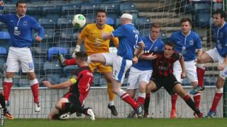 Crusaders captain Colin Coates heads towards the Linfield goal