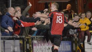 Crusaders Jordan Owens celebrates scoring the winner with fans at Seaview