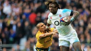 Marland Yarde of England evades a tackle from Will Genia of Australia