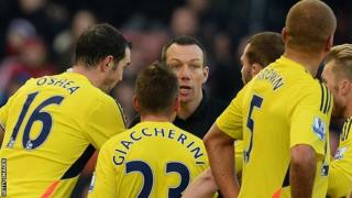 Referee Kevin Friend is surrounded by Sunderland players after sending off Wes Brown