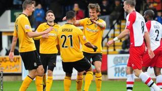 Harrison Dunk celebrates after scoring for Cambridge