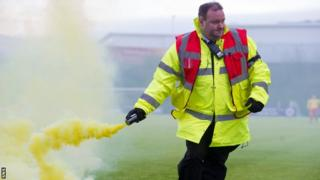 A steward gathers a flare from New Douglas Park on Saturday