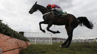 Barry Geraghty riding Sprinter Sacre jumps the last fence on his way to winning the third race of the day of The Melling Steeple Chase at Aintree in April 2013