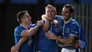 Michael Carvill and Andy Waterworth congratulate fellow forward Mark McAllister at Windsor Park