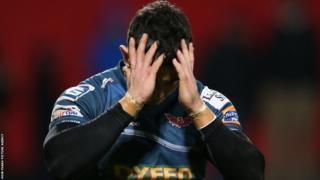 Winger Kristian Phillips holds his head in his hands as the Scarlets lose to an injury time try away at Munster