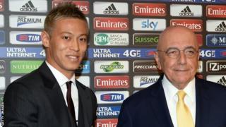 Keisuke Honda shakes hands with AC Milan's general director Adriano Galliani