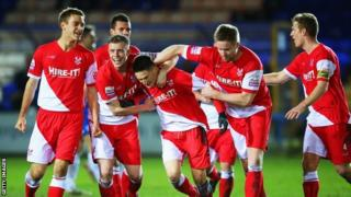 Joe Lolley celebrates Kidderminster's winner at Peterborough with team-mates.