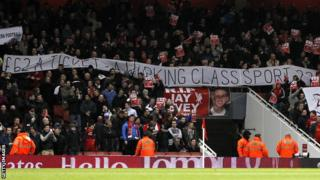 Liverpool supporters hold up banners inside the Emirates